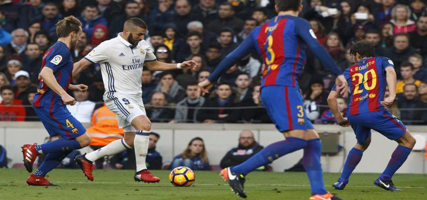 بنزيمة يحاول المرور من لاعبى برشلونة