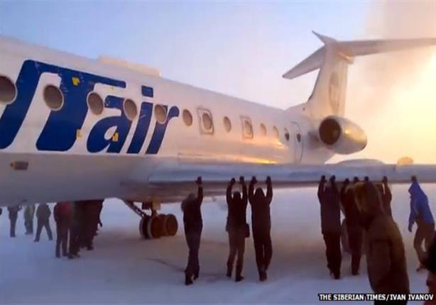 الركاب ينزلون من الطائرة ويدفعونها بأيديهم بسبب تجمدها