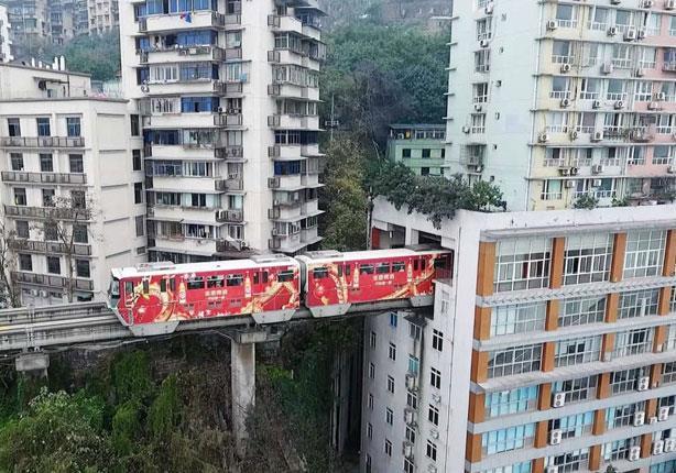 بالصور - الصين تواجه التكدس بقطار يخترق المباني السكانية