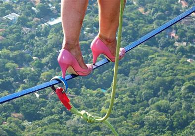 امرأة تغامر وتسير بالكعب العالي علي حبل في الهواء..بالصور