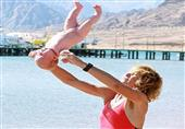 مدربة يوجا تؤدى حركات اليوجا لأطفال لم يتجاوزوا الشهر