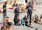 """بالفيديو والصور- الشرطة الفرنسية تجبر امرأة على خلع """"البوركيني"""" ودفع الغرامة"""