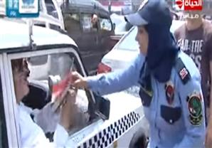 رجال الشرطة يوزعون أعلام مصرية وبرقيات تهنئة على المواطنين