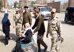بالصور- على كرسي متحرك.. رجال الجيش يساعدون مُسنًا للإدلاء بصوته في الشرقية