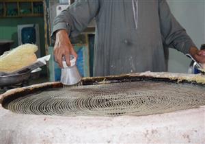 """بالصور- """"عم صلاح"""" شاهد على صمود الكنافة التقليدية أمام """"الآلية"""" في سوهاج: الصنعة مزاج"""