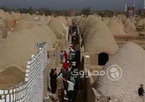 """بالصور- في مقابر """"البرشا"""" بالمنيا.. العيد رفقة الموتى"""