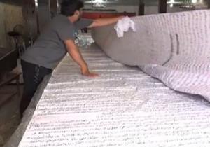 باكستانى يخطّ المصحف الشريف على 16 متراً من القماش