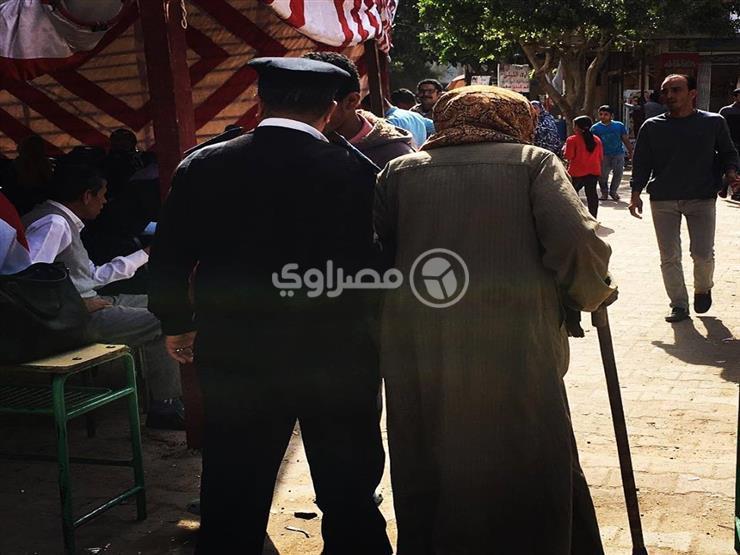 """شرطي يساعد """"مسن"""" أثناء دخوله للإدلاء بصوته ببولاق الدكرور"""
