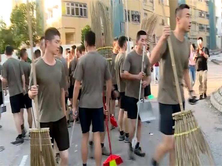 جنود صينيون ينظفون الشوارع خارج جامعة هونج كونج المعمدانية