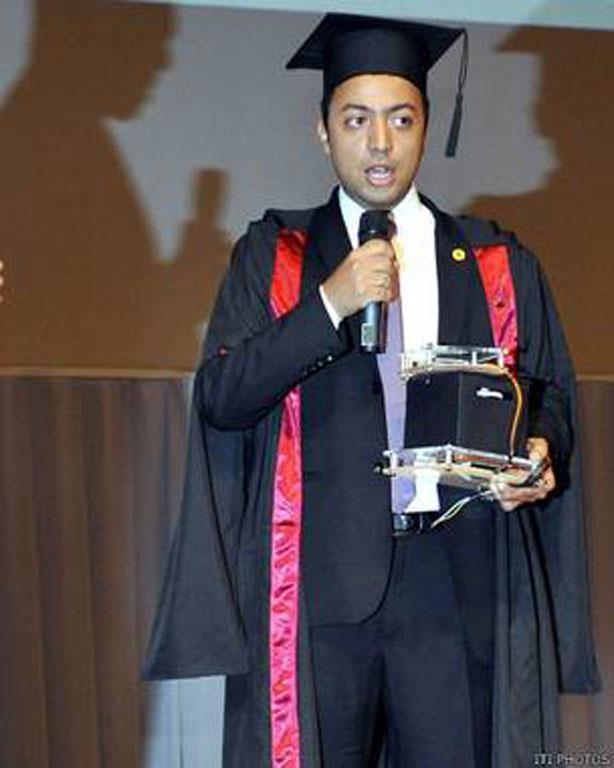 أحمد عساف في أثناء حفل تخرجه من المعهد، وهو يحمل العداد الذكي الذي يمكن من السيطرة على الاستهلاك في ظل أزمة الكهرباء المستعصية في مصر.