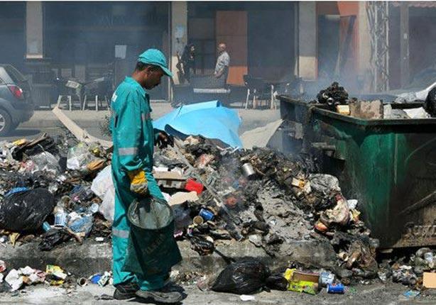 عامل تنظيف يحاول التعامل مع أكوام القمامة